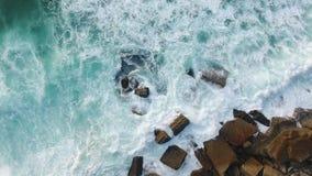 Ocean splash at rocky beach evening aerial view stock video footage