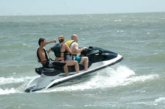 Ocean Sports. A three person wave runner in the ocean. A family riding a water sport vehicle in the ocean waves royalty free stock photo