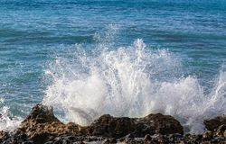 Ocean spray hitting the wet lava rocks on the Peloponnese peninsula of Southern Greece stock photography