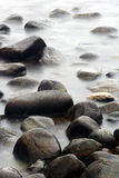 Ocean stones. Stones in the water in denmark on the north coast of the seeland island, slow shutter speed stock images