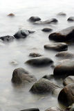 Ocean stones. Stones in the water in denmark on the north coast of the seeland island, slow shutter speed stock image