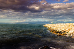 Ocean After The Storm. Ocean and breakwater made of rocks and concrete ith small lighthouse on its end after the storm Stock Photography