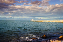 Ocean After The Storm. Ocean and breakwater made of rocks and concrete ith small lighthouse on its end after the storm Royalty Free Stock Photo