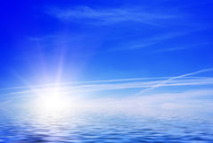 Ocean sunrise. Sea view - sun and clouds against blue sky Stock Photo