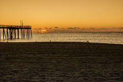 Ocean Sunrise. From beach next to pier Stock Image