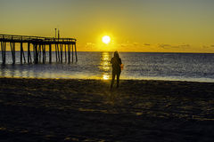 Ocean Sunrise. Lone woman on the beach next to a pier watching the sunrise Stock Photography