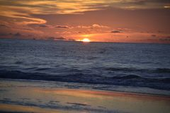 The sun begins to rise over the Atlantic Ocean and Amelia Island in a dramatic red  and orange color. The ocean sunrise is never the same from day to day when it royalty free stock photo