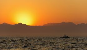 Ocean Sunrise. Orange sunrise at the ocean with mountains silhouettes Royalty Free Stock Image