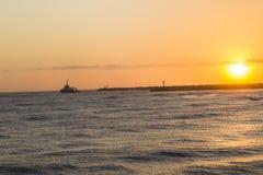 Ocean Sunrise Ship Harbor. Ocean sunrise ship tug exits harbor piers coastline landscape Royalty Free Stock Photography