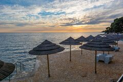 Free Ocean Sunrise With Grass Umbrellas Waiting For Early Guests. Stock Image - 170497291