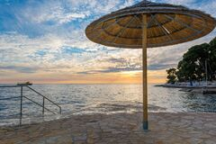 Free Ocean Sunrise With Grass Umbrellas Waiting For Early Guests. Stock Photo - 170497650