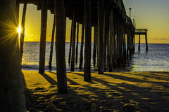 Ocean Sunrise. Through the wooded pier supports with star burst Royalty Free Stock Image