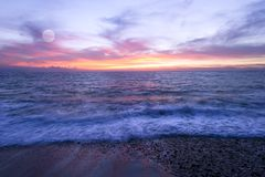 Ocean Sunset Beach Moon Wave. Moon rises over a colorful moon ocean beach sunset Stock Photography