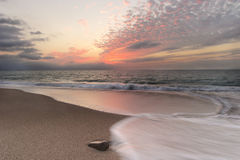 Ocean Sunset Beach Waves. Ovean Sunset beach waves is an images of a rush of waves captured by a time exposure with a glowing red sunset cloud filled sky on the stock image