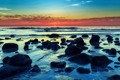 Ocean sunset. Colorful ocean sunset with stones at foreground Royalty Free Stock Image