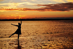 Ocean sunset dance. Silhouette of a woman doing ballet at the ocean during a golden sunset royalty free stock image