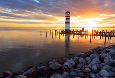 Ocean sunset with lighthouse Stock Images