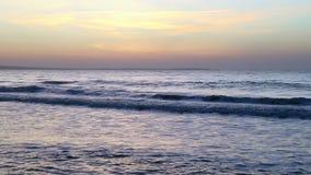 Ocean sunset panning left. Golden sunset ocean horizon. Sea waves blue water and orange sunlight. Beautiful landscape calm scenery. Serene tropical panorama stock video footage