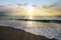 Ocean Sunset Rays. Is an ethereal ocean scenic with sun beams bursting forth from the setting sun as a gentle wave comes to shore royalty free stock photo