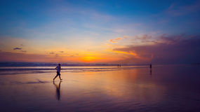Ocean sunset and a runner. Beautiful Indian ocean sunset, Bali island, Indonesia Stock Photos