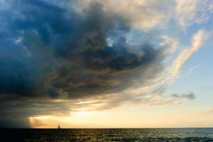 Ocean Sunset Sailboat Storm. Clouds is a powerful cloudscape with sun rays bursting over the open sea Stock Photography