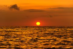 Ocean Sunset. Is a serene scenic seascape on the beach with the bright sun setting on the ocean horizon stock image