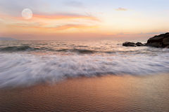 Ocean Sunset. Is a soft pastel colored beach setting with a detailed cloudscape and a gentle wave rolling to shore stock photography