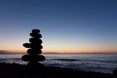 Ocean sunset with stacked stone silhouette Stock Photo