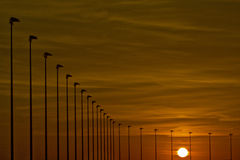 Ocean sunset and street lamps Royalty Free Stock Photos