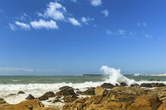 Ocean surf, blue sky and splash over the stones. Nature. Royalty Free Stock Images