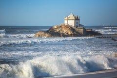 Ocean surf and Chapel Senhor da Pedra at Miramar Beach Royalty Free Stock Photography