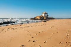 Ocean surf and Chapel Senhor da Pedra at Miramar Beach, near Porto Stock Photography