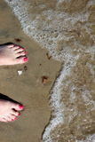 Almost. Ocean surf reaching up to pink painted toes Royalty Free Stock Image