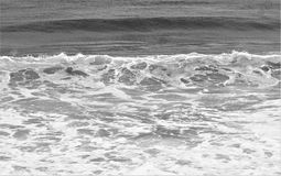 Ocean swells in black and white. Swells of ocean waves move onshore producing sea spray and white oxygen bubbles Royalty Free Stock Image