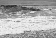 Ocean swells in black and white. Swells of ocean waves move onshore producing sea spray and white oxygen bubbles Royalty Free Stock Photography