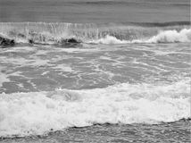 Ocean swells in black and white. Swells of ocean waves move onshore producing sea spray and white oxygen bubbles Stock Image