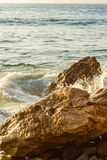 Ocean swirl around boulders with splash with ocean expanse texture. With skyline stock photography