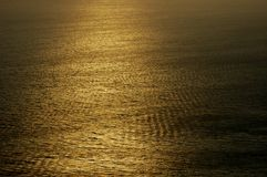 Ocean Texture. Abstract shot of the ocean with a high texture appearance. Shaft of golden light across water Royalty Free Stock Image