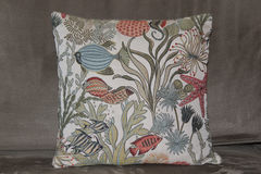 Ocean theme pillow with fish & plants on a couch Stock Photo