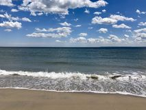 Waves on Beach During summer day. Ocean tide washes onto the sand on a cool, sunny afternoon in NYC Brighton Beach. Beautiful foam patterns form from the shallow Royalty Free Stock Photography