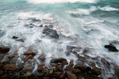 Ocean Tides Against Rocks. Long exposure showing the ocean waves flowing over the exposed coastal rocks royalty free stock photography