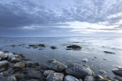 Ocean twilight scene with rocks in the foreground. Wide angle photo Royalty Free Stock Photo