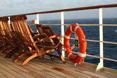 Deck chairs on cruise liner. Wooden deck chairs lined up at railing of cruise ship with view of open Atlantic Ocean waters on sunny day royalty free stock photo