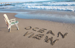 Ocean View. The words Ocean View written in the sand next to a beach chair and towel overlooking the beauty of the ocean on a nice clear sunny day Stock Photography