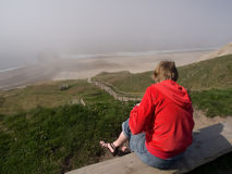 Ocean view. Woman sitting in the sun with view over misty ocean from high cliff Stock Photo