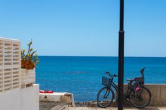 Ocean view with the bicycle with baby seat, flowers and towel with the shoe on it - Image royalty free stock image