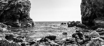 Ocean view from the bottom cliffs in Dorset England. View between rock, black and white photography Royalty Free Stock Photos