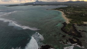 Ocean view and Mauritius landscape, aerial shot. Aerial shot of deep and shallow water of the ocean and coastline of green Mauritius Island with skyline mountain stock footage