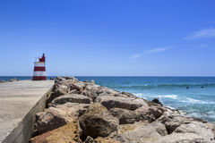 Ocean view and small lighthouse in the inlet jetty of Tavira Stock Photo