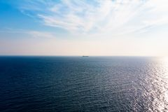 Ocean view in sunny summer day. Cargo boat on horizon. Ocean view in sunny summer day. Cargo boat on the horizon royalty free stock image